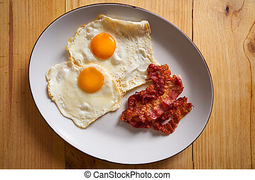 Breakfast bacon and eggs over easy on wood table