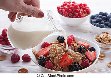 Breakfast - berries, fruit and muesli on white wooden