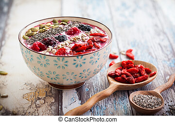 Breakfast berry smoothie bowl topped with goji berries, ...