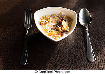 Breakfast bowl of cornflake and milk with spoon and fork in the morning.