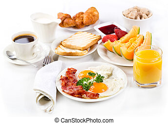 Breakfast with fried eggs, coffee, orange juice, croissant, toasts and fruits