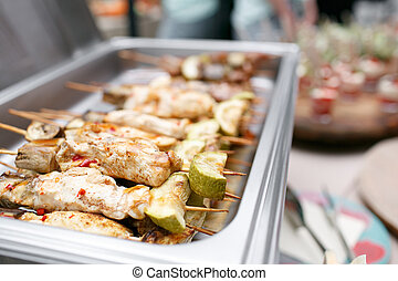 Breakfast buffet in hotel or catering. Grilled chicken on bamboo skewers.