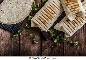 Breakfast burrito on wood board and wood table, eggs,...