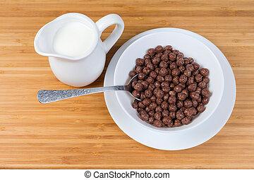 Breakfast cereal chocolate balls in bowl, milk in milk jug