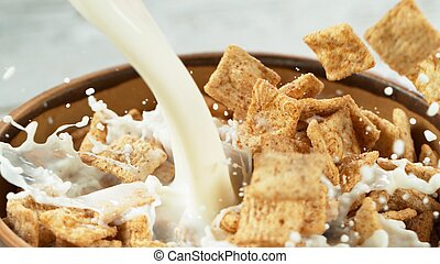 Breakfast cereals dropping into bowl with pouring milk, closeup