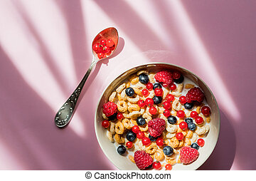Breakfast cereals rings in a white bowl. Oatmeal, corn flakes on a pink background. Breakfast or brunch buffet in a hotel or restaurant. whole grain cereal rings with berries. Tasty and healthy