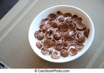 Breakfast Chocolate Cornflakes Cereal with milk in white bowl on the table