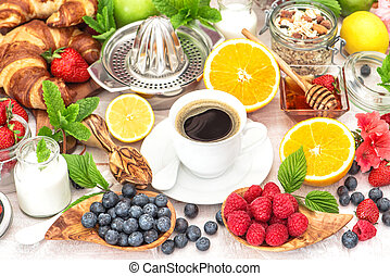 Breakfast coffee, croissants, muesli, honey, berries, fruits. Healthy food