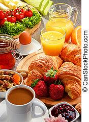 Breakfast consisting of croissants, coffee, fruits, orange...