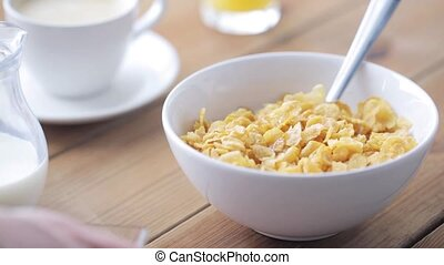 hand adding honey to corn flakes for breakfast - breakfast,...