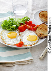 Breakfast - Fried Eggs, bread, tomato and lettuce on a plate