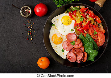 Breakfast. Fried eggs with sausage and vegetables in a...