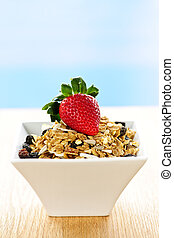 Bowl of granola cereal with fresh strawberry