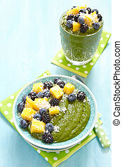 Breakfast green smoothie bowl topped with fruits