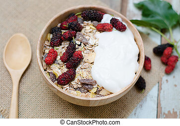 breakfast : home made yogurt with oat flakes in bowl on wooden