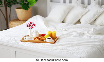 breakfast in bed of coffee, croissants, orange juice and fruit on tray
