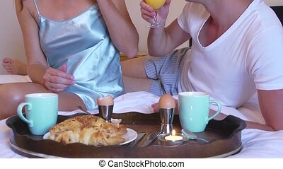 Breakfast in bed - Pan up over a young couple enjoying a ...