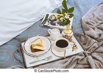 Breakfast in bed slice of Cheesescake with coffee cup flower in a tray and and reading book.