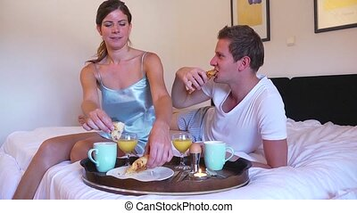 Breakfast in bed - Young couple enjoying a luxurious...