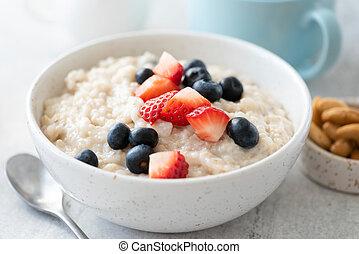Breakfast oatmeal porridge with strawberry, blueberry