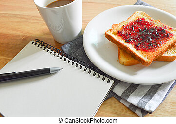 Breakfast of coffee and breads with notebook