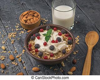 Breakfast of milk, yogurt, granola and berries on a wooden table.