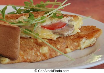 ham, cheese, tomato and mushroom omelette on plate