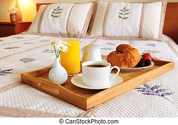 Tray with breakfast on a bed in a hotel room