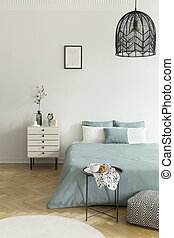 Breakfast on a metal table in front of a bed with sage green bedding in a natural bedroom interior. A beige drawer cabinet by the bed. Black lamp hanging from a ceiling. Real photo