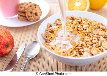 Breakfast pouring milk into corn flakes creating splash apple and orange fruit