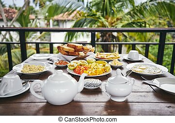Breakfast ready to eat. Eggs, tropical fruit, toasts and tea...
