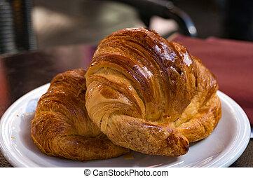Breakfast scene. Croissant on white plate
