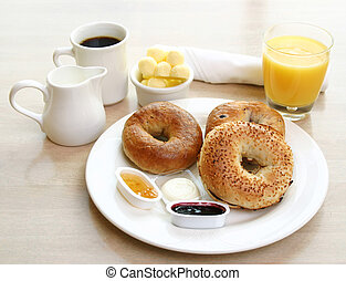 Classic breakfast of assorted bagels, toast, butter and orange juice