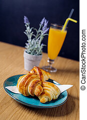 Breakfast served with croissants, coffee and orange juice