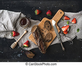 Breakfast set. Black baguette toasts with fresh strawberries, honey and mascarpone cheese on dark grunge table surface, top view
