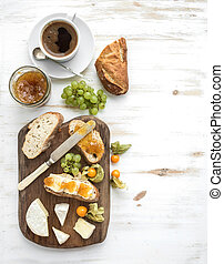 Breakfast set. Brie cheese and fig jam sandwiches with fresh grapes, ground cherries. Cup of coffee. Top view, copy space
