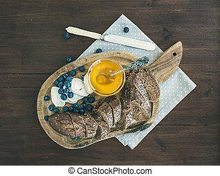 Breakfast set on a dark wood background: fresh dark baguette cut