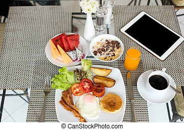Breakfast set on the table with pancakes, bacon, eggs and coffee