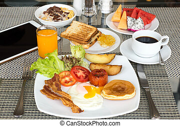 Breakfast set on the table with pancakes, bacon, eggs and ...