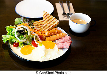 Breakfast set, with vegetable salad, ham, bacon, fried egg, sausage and cup of coffee on table.