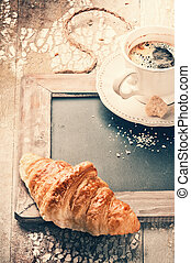 Breakfast setting with coffee and fresh croissant
