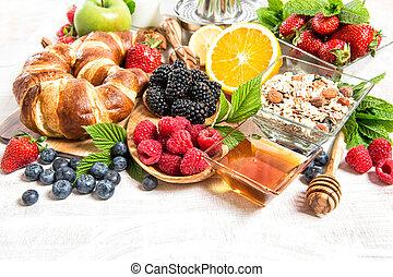 Breakfast table setting with croissants, muesli, fresh berries, fruits orange, apple, milk. Healthy nutrition