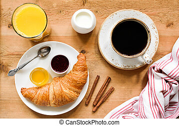 Breakfast table with coffee, croissant, jam, orange juice and jam