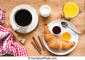 Breakfast table with croissant, coffee, orange juice and jam