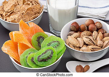 Breakfast. Three bowls of nuts, cornflakes, dried kiwi and mango. Glass of milk. Healthy eating.