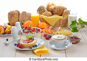 Colorful breakfast with cappuccino, fruit, fresh orange juice, ham, cheese and fresh rolls
