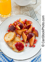 Breakfast toasts with jam, plum and pomegranate seeds