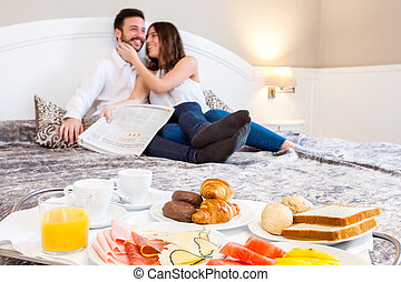 Breakfast tray with couple in background.