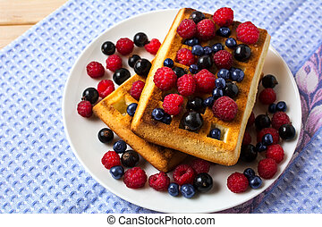 Breakfast waffles with fresh berries on the blue linen napkin