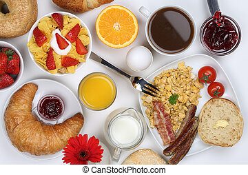 Breakfast with a cereals, bagels, scrambled eggs, marmalade, coffee and orange juice from above